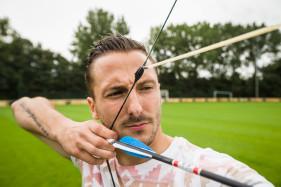 Danijel Milicevic, profvoetballer bij KAA Gent doet zijn overwinningssymbool met een echte pijl en boog.