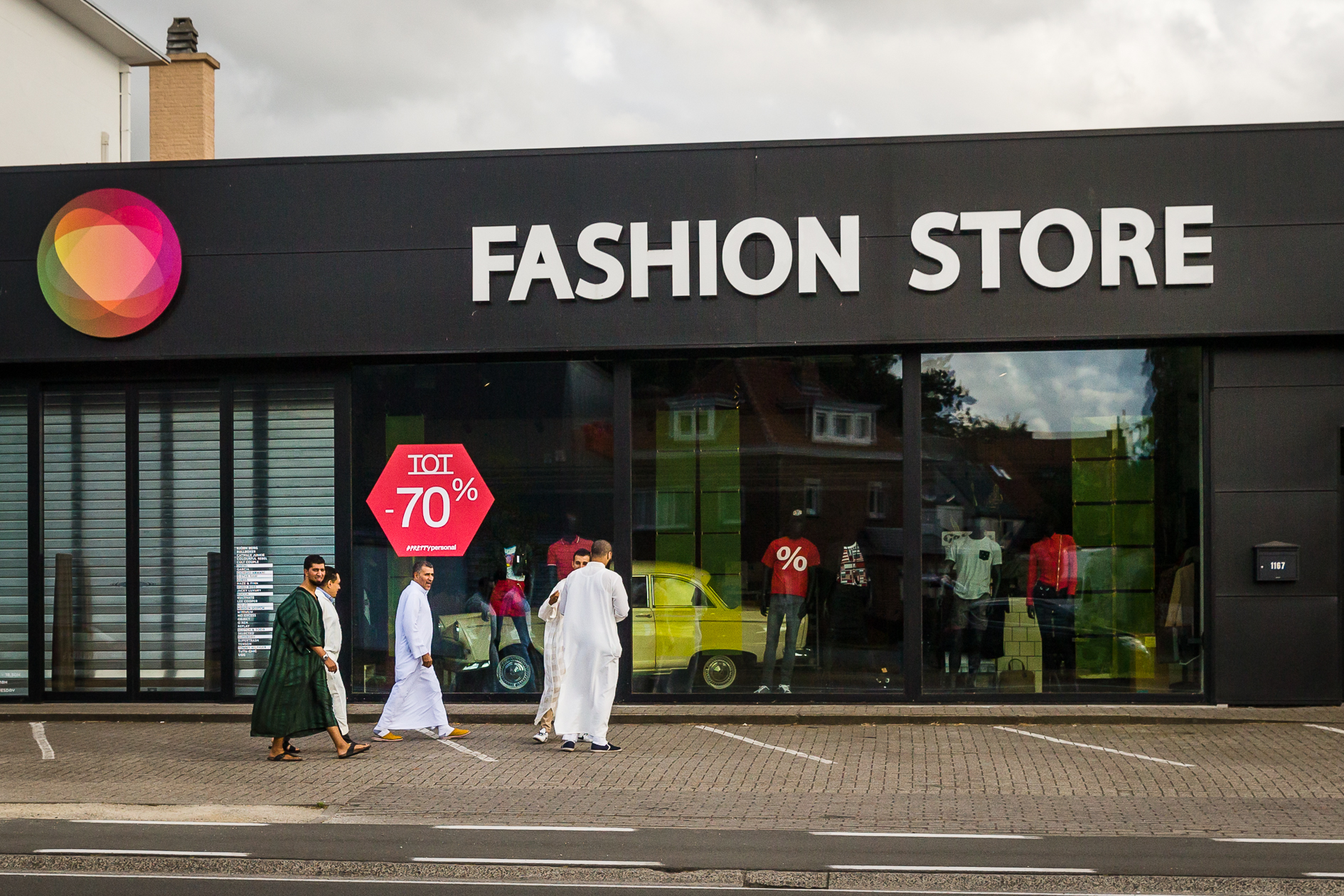 Muslim men dressed in traditional clothing go shopping for sales at a fashion store in Gent.